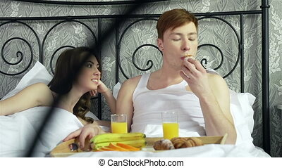 Snack In Bed - Resting lovers sharing snack while being in...