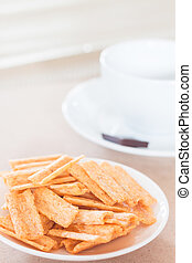 Snack on white plate with coffee cup