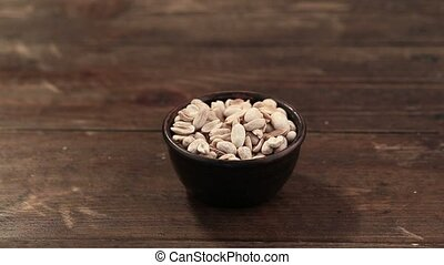 snack peanuts in a plate on a wooden background. a...