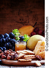 Snack plate: grapes, pears, hazelnuts, almonds, walnuts, cheese Maasdam and honey, selective focus