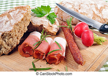 Snack with bacon and sausage - Tyrolean rye bread with...