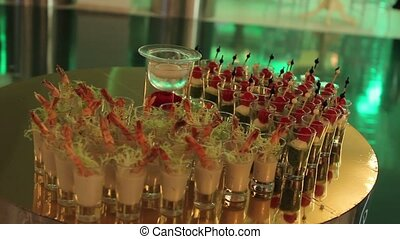 Snacks on buffet table, Canapes of cheese vegetables meat and seafood, Glasses with seafood snacks, banquet dish