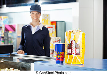 Snacks On Concession Stand At Cinema With Worker In Background