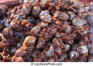 Snails with spicy tomate sauce for sale at a market stall