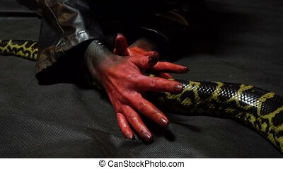 Snake and bloody hands - Footage of woman with bloody hands...
