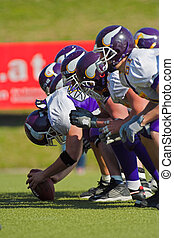 Snap - Football team at the line of scrimmage. The center is...