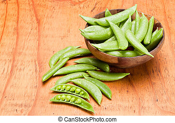 Snap Peas - Fresh snap peas in a wooden bowl on a wooden ...