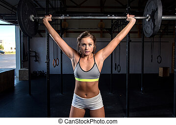 Snatch Overhead - A young fit woman doing a snatch at a gym