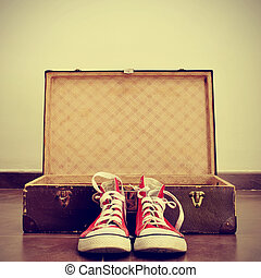 sneakers and old suitcase - a pair of red sneakers in front...