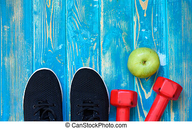 Sneakers, earphones and drinking water on blue background. Sport equipment. Healthy