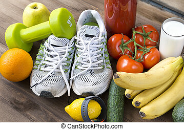 sneakers ,oranges, tomatoes, Apple, pear ,lemon, sports bracelet, tomato juice ,bananas, milk, fruits and vegetables on a brown wooden background