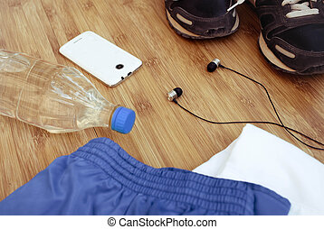 Sneakers, water, earphones and phone on wooden background.