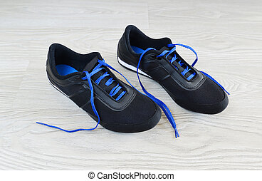 Sneakers with blue laces are on  floor
