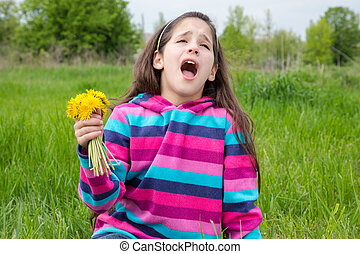 Sneezing girl sitting on green meadow and holding bouquet of dandelions