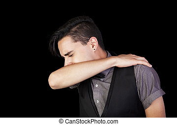 Sneezing Man - A young man sneezing into his elbow. Black...