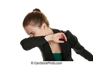 A young business woman, sneezing into her sleeve to prevent spreading germs. Shot on white background.