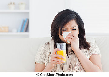 Sneezing woman drinking a glass of orange juice in a living...