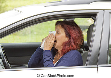 Sneezing woman in the car