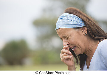 Portrait attractive mature woman outdoor suffering from seasonal hayfever or cold ro flu, sneezing, with hand on nose, closed eyes, with blurred background and copy space.