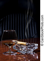 Snifter glass of cognac and cigar