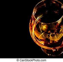 snifter of brandy in elegant typical cognac glass on black...