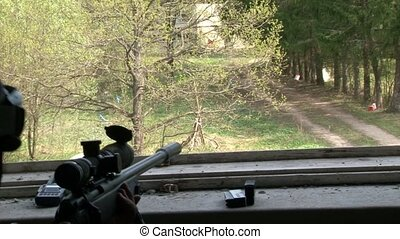 Sniper in military uniforms with weapon in position in a destroyed house.