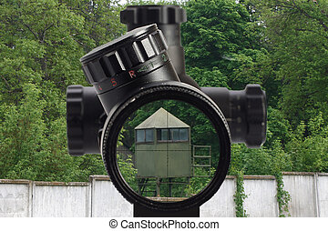 sniper look through the optical sight at a military base