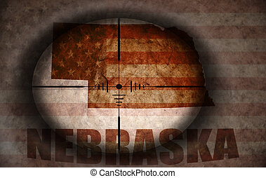 sniper scope aimed at the vintage american flag and nebraska state map