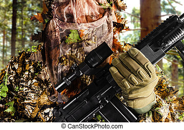 Sniper soldier in masking forest suit.
