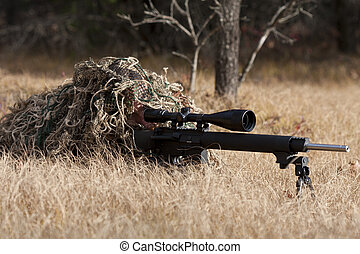 sniper laying on the ground covered in a ghille suite tall...