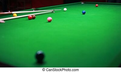 Snooker player hits ball...