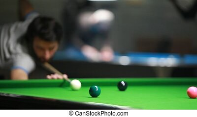 Young man playing billiard (snooker)