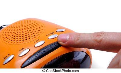 Snooze Alarm - Finger pressing a snooze alarm button