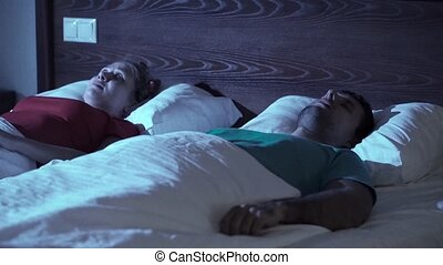 Snoring man. Couple in bed, man snoring and woman can not sleep, covering ears with pillow for snore noise. Young interracial couple sleeping in bed at home