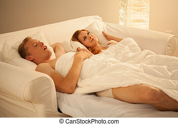 Snoring mans sleeping in bed with his irate wife