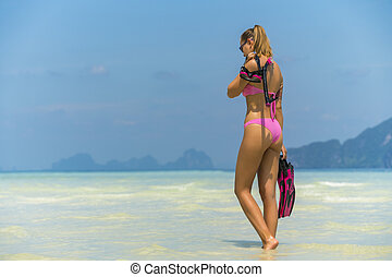 Snorkel girl with scuba mask and snorkeling fins relaxing on Thailand beach travel summer vacation. Ocean watersport tropical fun.