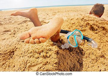 Snorkel, mask and boy feet buried in sand beach
