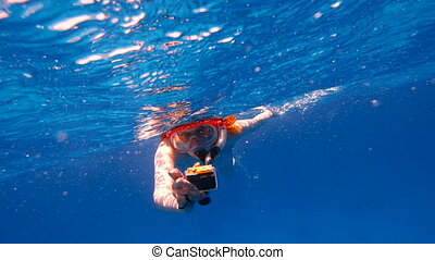 Snorkeling Girl with an action camera floats in the sea and shoots a video camera