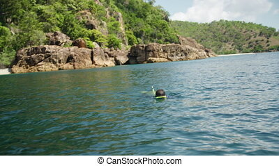 snorkeling in a blue diving suit - A man in a blue diving...