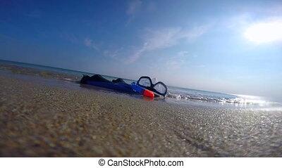 Snorkeling set in the surf on sandy beach sun shining in sky