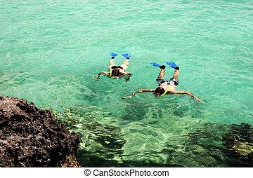 Snorkel diving in emarald water near Rivera Maya shore