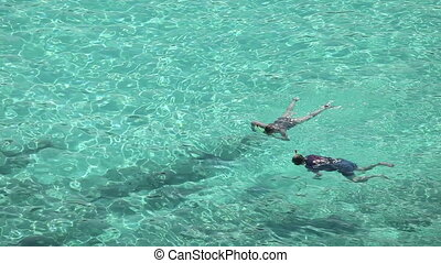 Snorkeling - Man and woman snorkeling in the clear sea water...