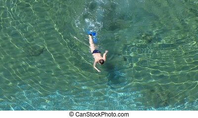 Snorkeling - Man swims in the clear sea, view from above