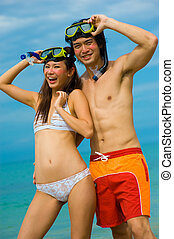 A young couple with snorkelling gear on a tropical beach