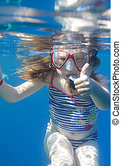 a young girl snorkelling in clear blue sea on holiday