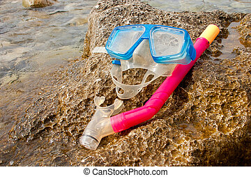 Snorkling - 2 - Blue snorkel goggle and tube on a rock near...
