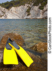 Snorkling - 3 - Yellow flippers on a rock near the sea