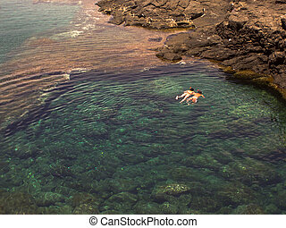 snorkling in crystal clear water in a natural basin in Lanzarote, Spain at the coast