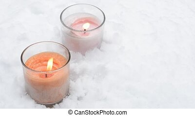 Snow and glass candles - Falling snow and two glass candles ...