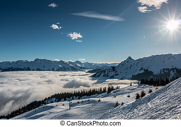 Snow and sun on the top of the mountains and fog down the...
